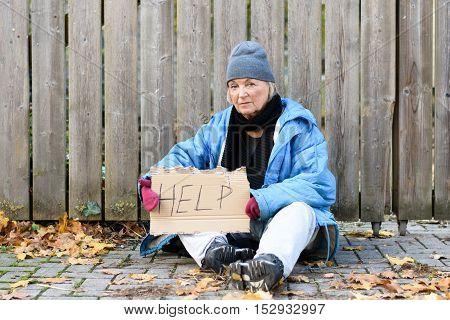 Elderly Homeless Woman Sitting On The Street