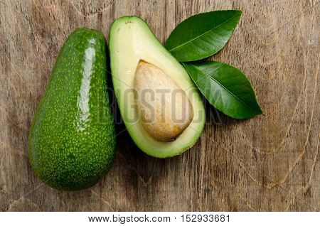 Fresh Avocado With Leaves On Wooden Background