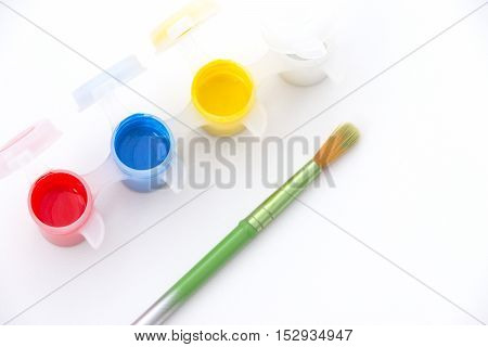 Paint pots with vibrant red yellow blue and white paint alongside a green paintbrush