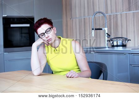 woman in yellow dress sitting at kitchen table and sleeping