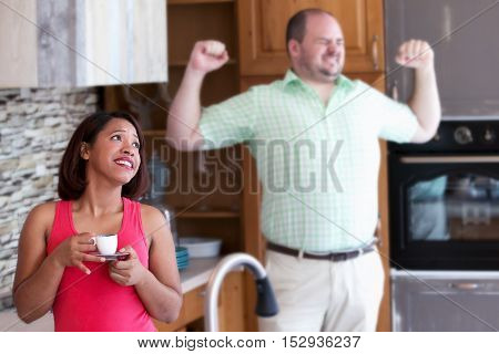woman drinking coffee in kitchen looking annoyed while man is yawning