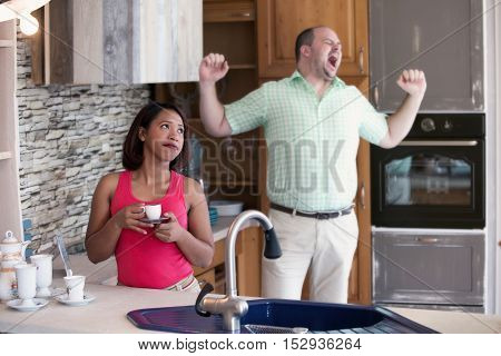 beautiful hispanic woman drinking coffee in kitchen and man is yawning
