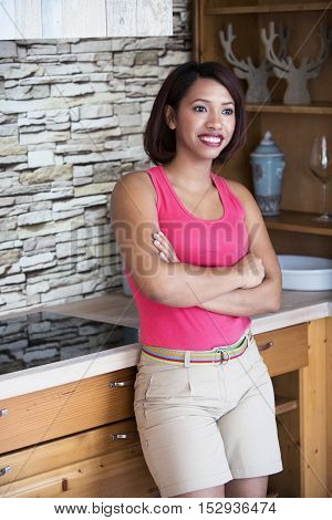 beautfiful hispanic woman standing in kitchen and smiles