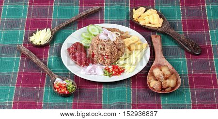 Popular Thai food ,Fried jasmine rice with shrimp paste,(Kao Klok Kapi) with green mango roll,Chinese sausage,crispy dried fish,shrimp,chili,shallots,stir sweet pork,cucumber and scrambled egg .