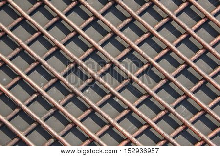 The grid of thick rods and its shade from the sun. Rods made of nonferrous metal. Texture background