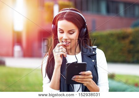 Woman online flirt and listening music outdoor on tablet in sunset