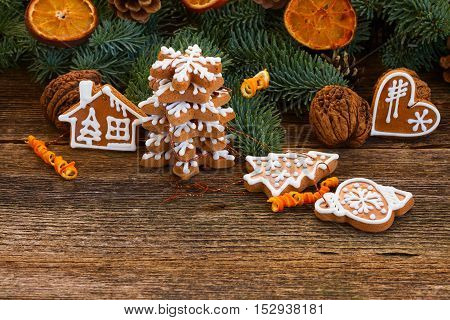 christmas gingerbread cookies with fir tree twigs and oranges on wooden table