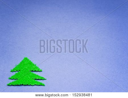 green Christmas tree cut from plush material on surface of the blue paper