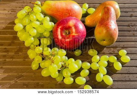 Grapes, pears and apples on a rustic wooden background