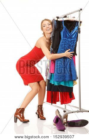 Young woman stands near her clothes rack with lots of dressesand embraces clothes.