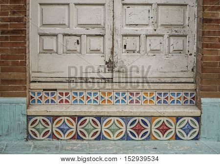 wooden door and steps decorated with colorful tiles in Spain