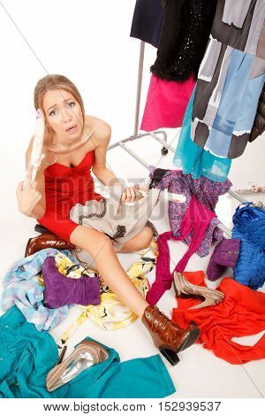 Young woman sits near her clothes rack with lots of dressesand some clothes is on the floorand she is holding her dresses and scream!