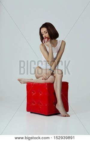A thoughtful girl with apple sitting on a read cube against neutral background