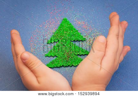 children's hands to protect Christmas tree cut from a plush green sprinkled with colored glitter on a blue paper background
