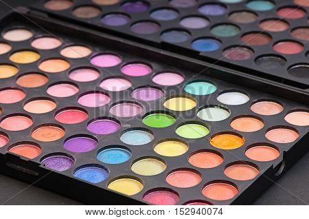 a Make-up colorful eyeshadow palettes isolated on black background