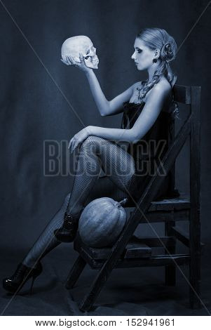 Beautiful woman with a skull and pumpkin low key portrait