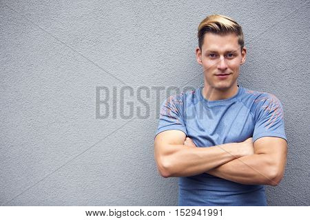 portrait of handsome blond young sportsman smiling at camera