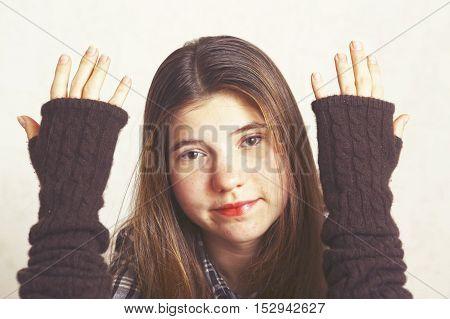 Teen pretty girl show hands in woolen fingerless mittens close up portrait. Girl teenager.
