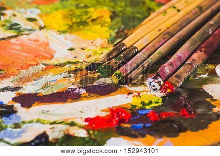 Palette with old paints and artistic brushes