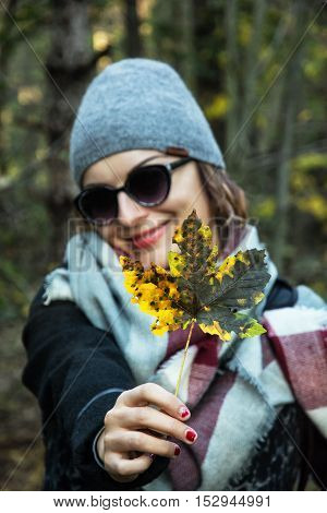 Young caucasian woman with colorful maple leaf in autumn outdoors. Positive emotions. Seasonal natural female portrait. Beauty fashion and nature.