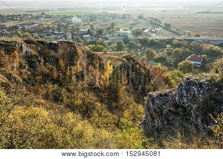 Seasonal natural outdoors scene. Rocks colorful trees village and fields. Vibrant colors. Beauty in nature.