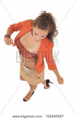 Full-length portrait young elegant woman in brown skirt, orange jacket and brown bra. Fashion studio shot.