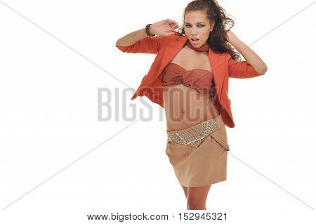 Sexy beautiful woman posing in studio on white background, wearing orange jacket, brown fashionable skirt. Full photo. Girl looking at camera.
