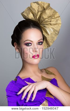 Beautiful brunette young woman with smoky eyes make-up and golden head accessory. Beauty shot over grey background. Copy space.