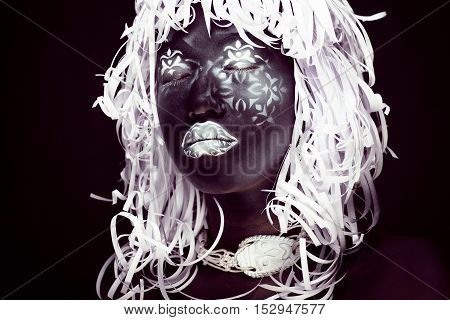 creative makeup like Ethiopian mask, white pattern on black face close up, halloween horror, fashion style print