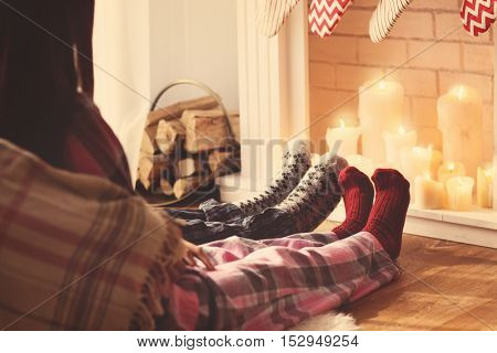 Couple legs resting in front of fireplace at home in Christmas holiday