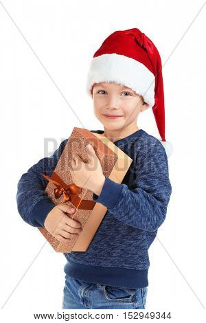 Cute little boy in Santa hat with Christmas gift on white background