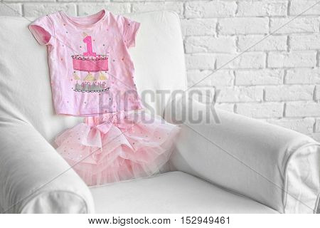 Cute pink skirt and T-shirt for girl on armchair, indoors