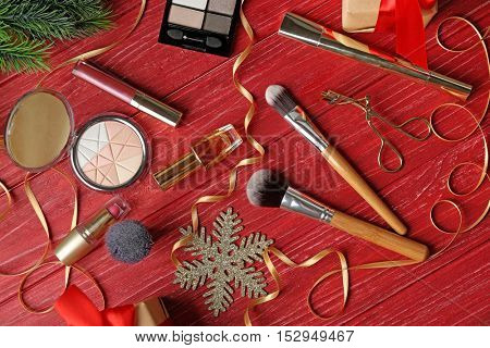 Brushes with colorful makeup cosmetic on red wooden background