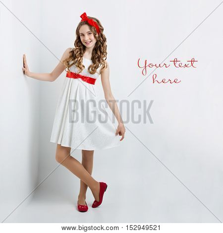 Beautiful teenage girl with long curly hair and red ribbon bow on head wearing white dress standing near wall. Happy expression. Studio portrait on white background. Copy space.