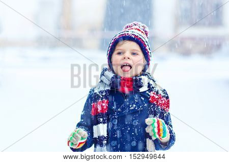 Winter portrait of little kid boy in colorful clothes, outdoors during snowfall. Active outdoors leisure with children in winter on cold snowy days. Preschool child tasting snow