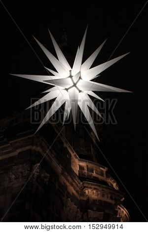Street decorated with Christmas star at night.