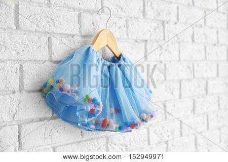 Cute skirt for girl hanging on white brick wall background