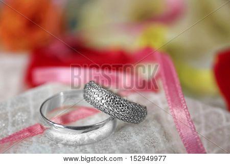 Beautiful wedding rings on white fabric background