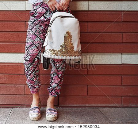 Young woman with fashion details on brick wall background