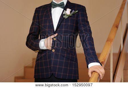 Stylish groom on stairs