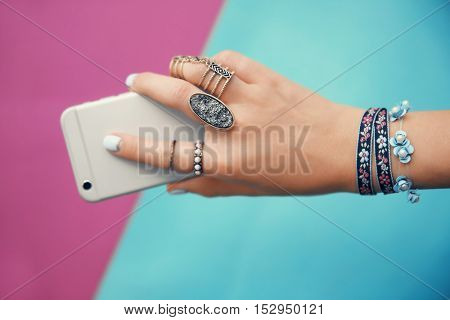 Female hand with jewelry and cellphone on color background