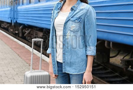 Young woman with suitcase standing on railway platform, closeup