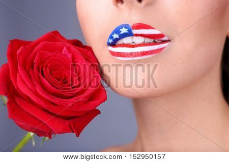 Girl with USA makeup and red rose on grey background