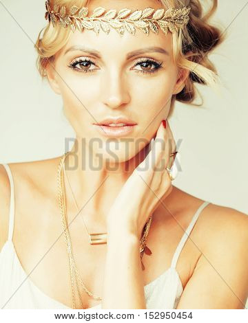 young blond woman dressed like ancient greek godess, gold jewelry close up isolated, summer trends