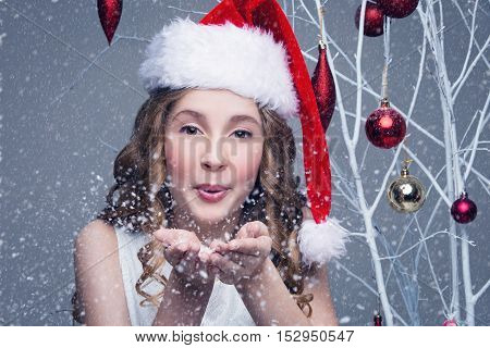 Beauiful girl in red santa cap blowing snow off palms of hands. Happy expression. Studio shot on christmas ornament background with falling snow. Copy space.