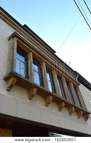 Six windows of facade with yellow stone frame and columns of reinforcement.