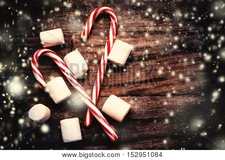 Christmas Decorations - Candy cane with white marshmallows winter holidays symbol on wooden vintage background