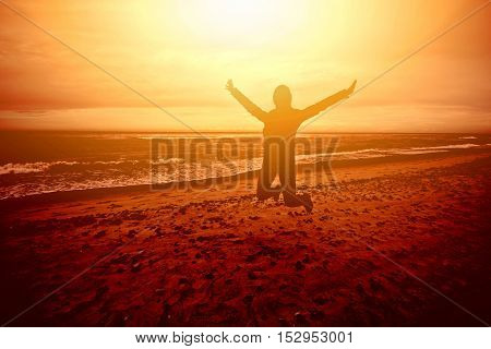 Figure person jumping on the beach at sunset. Joy freedom happiness etc positive concept.