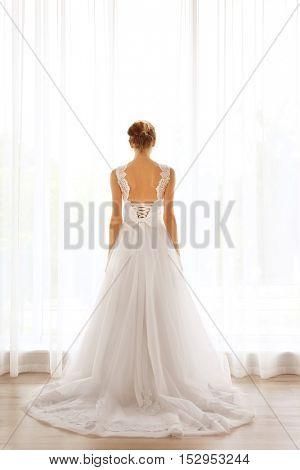 Bride in a beautiful wedding dress standing near window