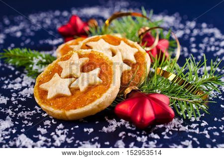 Cookies from puff pastry with jam on the background of Christmas decorations. Selective focus.